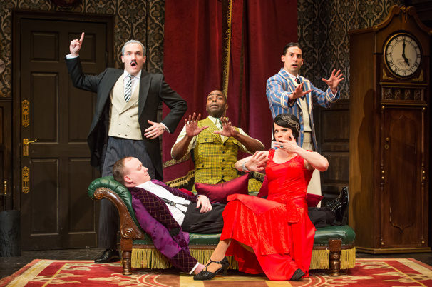 The actors of the play gesturing comedic antics and posing in character