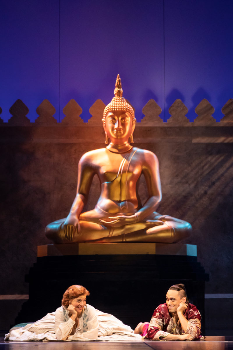 Anna and the King of Siam lie on the floor underneath a Budha statue.