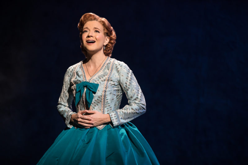 Anna in a green dress with hoop skirt sings on stage.