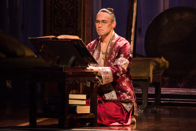 The King of Siam wears eyeglasses to read a large book