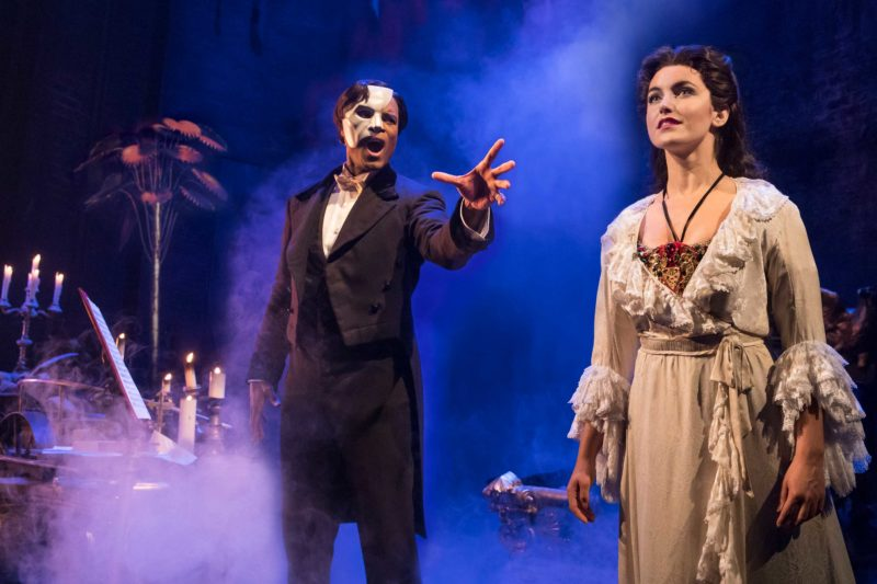 The Phantom of the Opera sings to his young voice student, Christine, who stands facing away from him and entranced by his song.